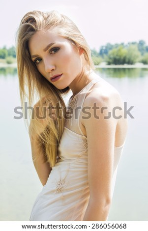 Sexy blonde girl posing on the lake shore