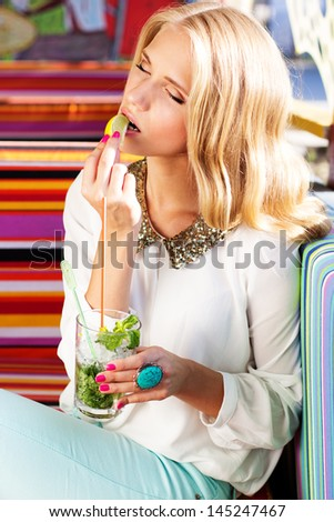 Sexy blonde girl resting outdoors on colorful sofa and drinking mojito