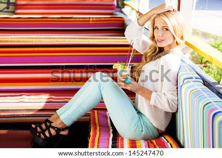 Sexy blonde girl resting outdoors on colorful sofa and drinking mojito - stock photo