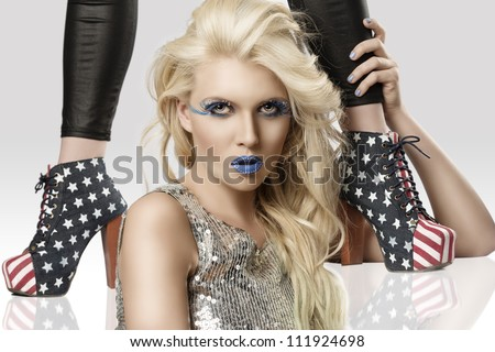sexy blonde girl with euro flag make-up and glitter dress with two shoes with american flag design, she looks in to the lens with actractive expression and she takes the ankle of the model behind her - stock photo