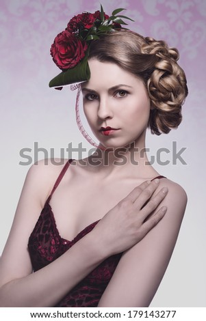 sexy blonde girl with romantic floral hair-style, sexy red dress and heart shaped lipstick. Red roses in the hair