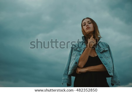 sexy blonde haired young woman posing against dark moody sky in light of setting sun
