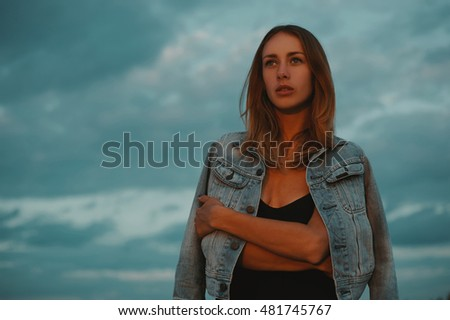 sexy blonde haired young woman posing against dark moody sky in red light of setting sun