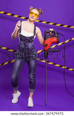 sexy blonde in denim overalls and protective glasses is building on a blue background with the protective tape on the drill hammer resting.