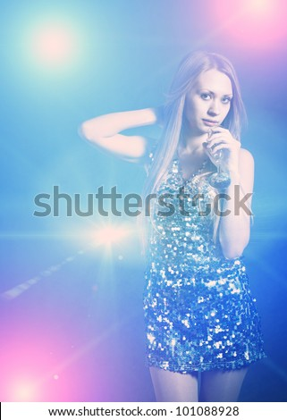 Sexy blonde in party dress girl dancing in discolight - stock photo
