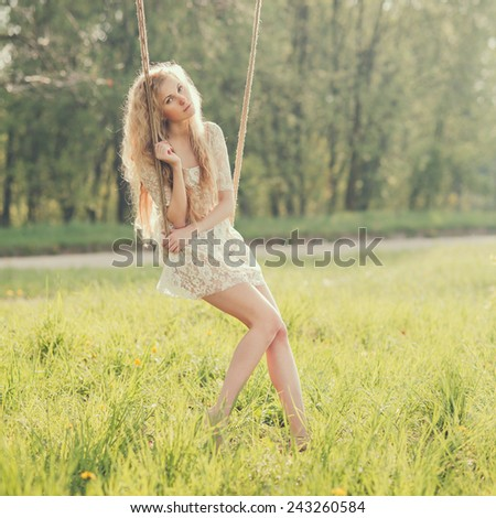 sexy blonde in the morning on a swing in the park - stock photo