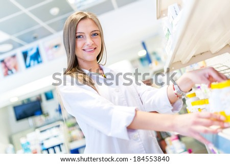Sexy blonde pharmacist selling antibiotics and prescription drugs - stock photo