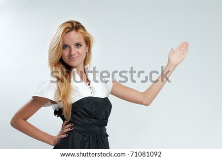 Sexy blonde pointing to the blank space. Lady against grey background wearing fashionable dress studio shot. - stock photo