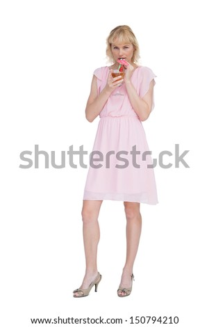Sexy blonde posing while drinking cocktail and looking at camera against white background - stock photo