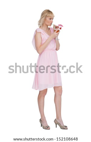 Sexy blonde posing while drinking cocktail and looking away against white background - stock photo
