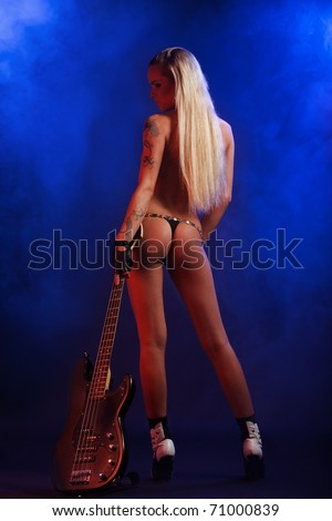 sexy blonde posing with guitar over blue smoky background - stock photo