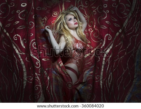 Sexy blonde with a melancholy red and gold armor, burlesque image on fabric decorated with golden threads - stock photo