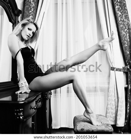 sexy blonde with long legs posing next to the mirror - stock photo