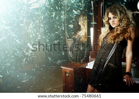 Sexy blonde woman and shattered glass fragments