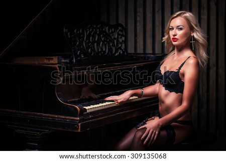sexy blonde woman in black lingerie sitting near piano Fashion studio portrait - stock photo