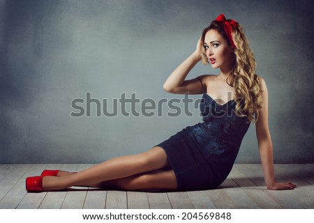 sexy blonde woman in jeans sundress and red shoes pin up girl retro woman sexy legs and a red capitium on his head crawling on the floor  sitting on the floor and straightens hair