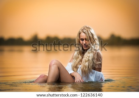Sexy blonde woman in lingerie in a river water.Sexy young woman relaxing on the beach.Young, beautiful woman in the evening swim in the river.Beautiful young woman in a white bathing in the river. - stock photo