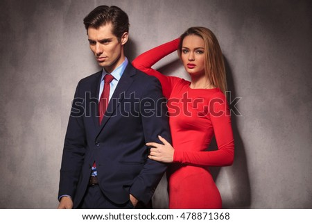 sexy blonde woman in red dress leaning her elbow on her boyfriend's shoulder
