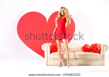 Sexy blonde woman in red dress posing with big heart. St. Valentine's day. Studio shot. - stock photo
