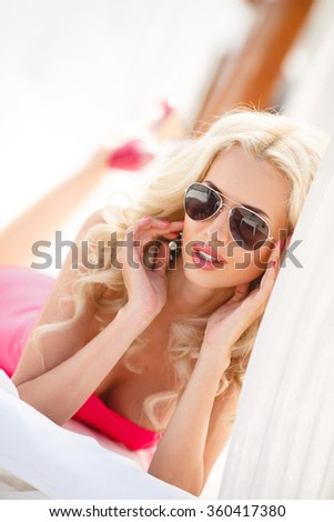 sexy blonde woman in summer dress. fashion outdoor photo of beautiful sexy woman with blond hair wearing elegant pink dress , relaxing on yacht. Beautiful sexy young brunette woman with long wavy hair - stock photo