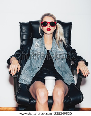Sexy  blonde woman in sunglasses sit on black office chair and holding a cup of coffee knees. Fashion hipster girl. White background, not isolated - stock photo