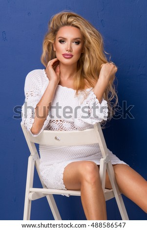 Sexy blonde woman in white dress on chair