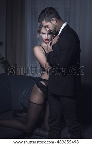 Sexy blonde woman lover in underwear cuddle to stylish man at night