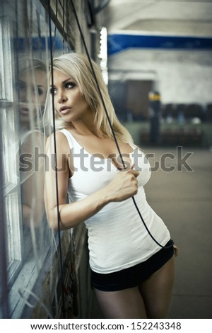 Sexy blonde woman posing in  hall