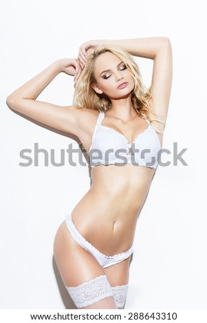 Sexy blonde woman posing in white underwear at wall - stock photo