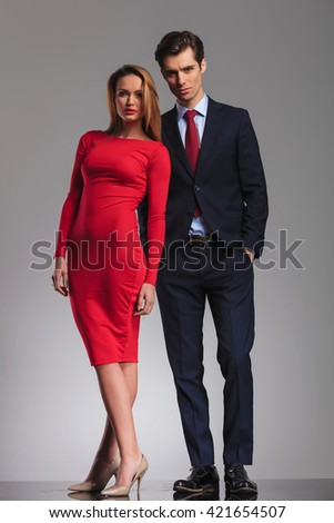 Sexy blonde woman red dress standing next to Young businessman with hands in pockets in studio