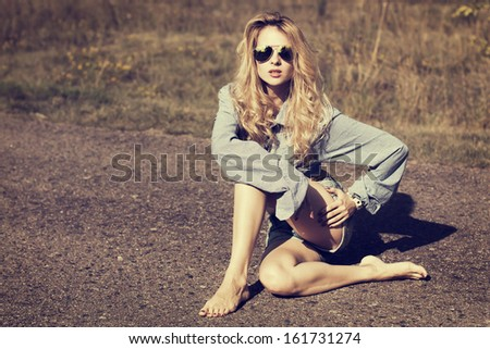 Sexy Blonde Woman Sitting on the Road. Toned Photo.