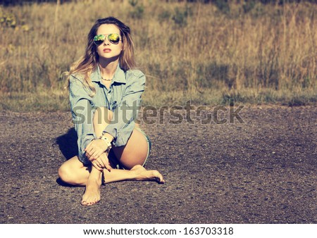 Sexy Blonde Woman Sitting on the Road. Toned Photo. - stock photo