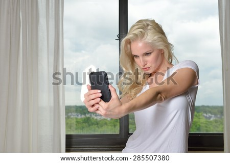 Sexy blonde woman wearing a white t-shirt - takes a photo of herself - selfie - stock photo