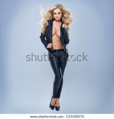Sexy Blonde Woman Wearing Jacket On Blue Background - stock photo