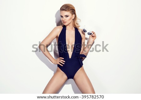 Sexy blonde woman wearing navy blue swimwear with sunglasses posing on white background. Perfect body - stock photo