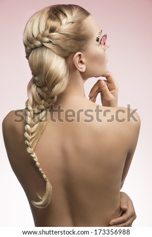 sexy blonde woman with cute long braid hair-style and creative feathered make-up showing her sensual nude back  - stock photo