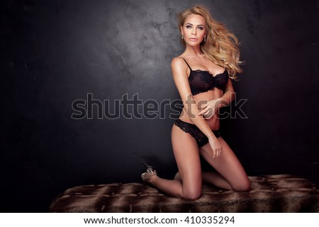 Sexy blonde woman with fit body posing in black lingerie. Full photo.