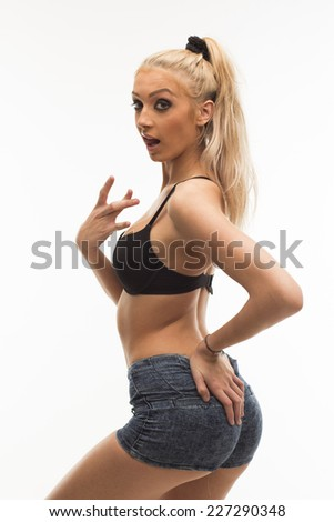 Sexy blonde young woman in jeans shorts and bra on white isolated background