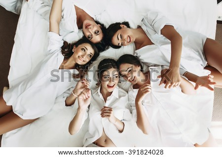 Sexy bride & bridesmaids lying in bed before wedding - stock photo