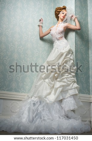 Sexy bride in long white wedding dress leaning against wall - stock photo
