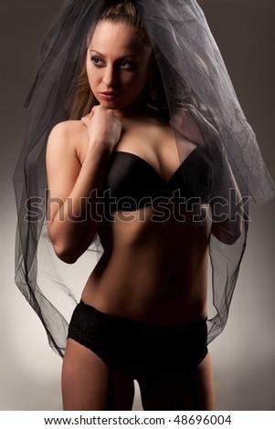 Sexy bride in veil and black lingerie studio portrait - stock photo