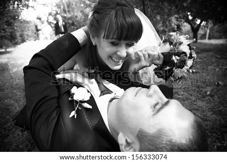 Sexy bride lying on top of groom in park - stock photo
