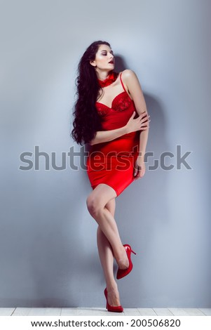 sexy brunette girl in a red skirt and red corset and red shoes with red garter stands near gray wall and wooden floor in a studio  pin up - stock photo