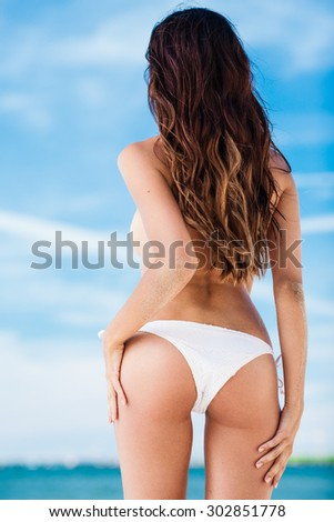 Sexy brunette girl in white swimsuit posing on a beach - stock photo