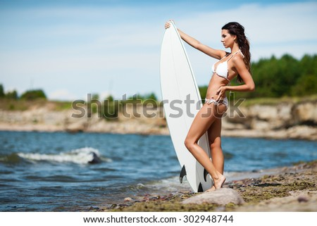 Sexy brunette girl in white swimsuit posing with a surfing board on a beach - stock photo