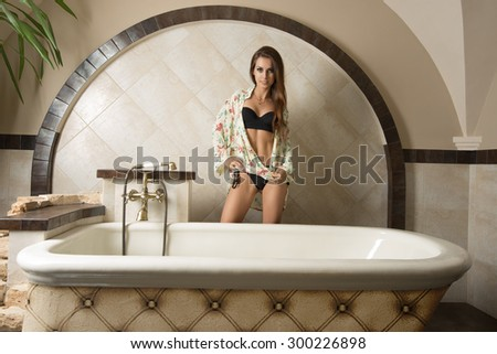 sexy brunette girl posing near bathtub in elegant retro bathroom with black lingerie, floral shirt and long natural hair-style. Looking in camera   - stock photo