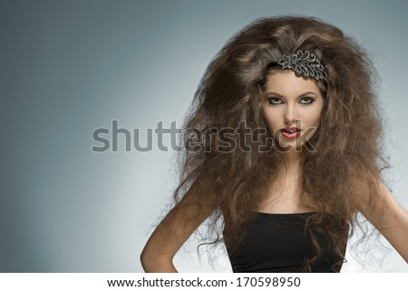 sexy brunette girl with long curly voluminous hair-style and glitter accessory in the hair posing in fashion portrait with cute make-up  - stock photo