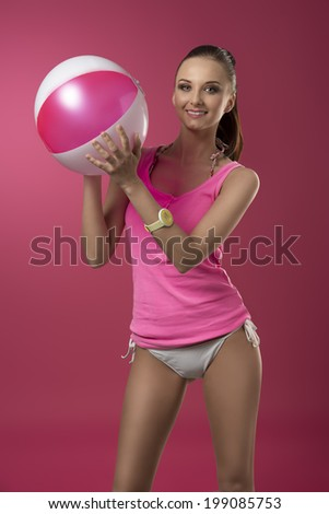 sexy brunette girl with ponytail and pink singlet on bikini playing with fun expression with beach ball