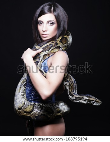 sexy brunette holding python over black background - stock photo