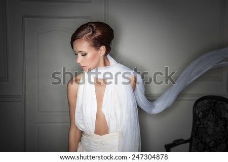 sexy brunette in a beautiful white dress with a deep cut on his chest . looking down - stock photo